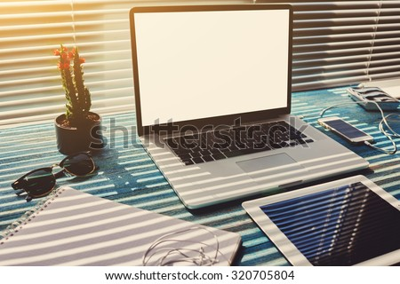 Freelance desktop with accessories and distance work tools, blank screen laptop computer and digital tablet, mouse, sunglasses, phone charging and touch pad, business workspace in home or office