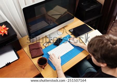 Freelance developer and designer working at home, man using desktop computer.