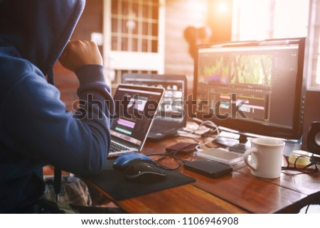 Freelance editor man working editing video in house office  for upload to social media.