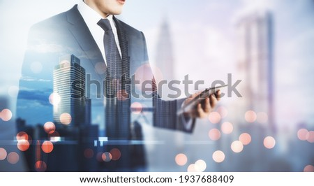 Freelance mobile working concept with man in black suit looking at digital tablet on blurry megapolis city background. Double exposure