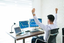 Freelance stock broker celebrating successful trading while sitting with arms raised and working at home