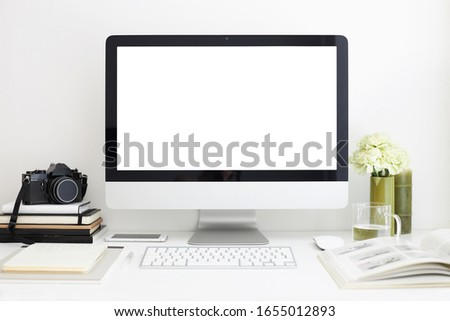 Freelance, work and creativity concept. Modern cozy workspace of photographer with peony flowers, magazine, stationary items, camera and computer with blank screen on desk. Selective focus