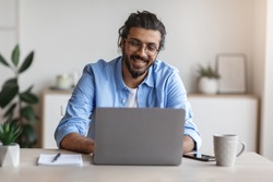 Freelance Work. Happy Millennial Indian Man Working On Computer At Home Office, Sitting At Desk With Laptop, Handsome Western Guy Looking At Device Screen And Smiling, Enjoying Remote Job, Copy Space