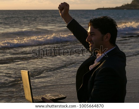 Freelancer and employee enjoys the work done on the laptop. A man is sitting on the sea. #1005664870