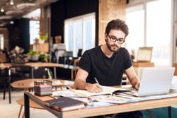 Freelancer bearded man in t-shirt taking notes at laptop sitting at desk.