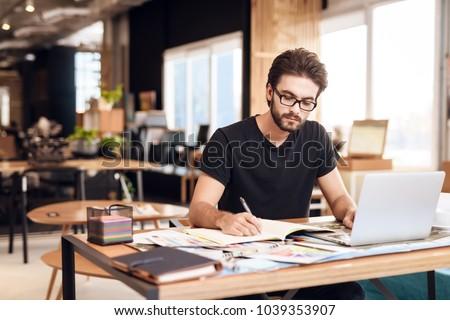 Freelancer bearded man in t-shirt taking notes at laptop sitting at desk. Stock photo ©