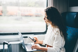 Freelancer girl working with laptop in the train. Girl looking to the phone in her hand. Business travel or technology concept.