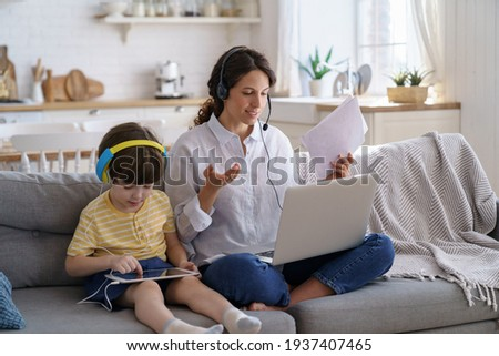 Freelancer mother sit on couch at home office during lockdown, remote work on laptop. Child using tablet, playing in game at tablet, sitting with mom on sofa. Family, telework, e-learning concept.
