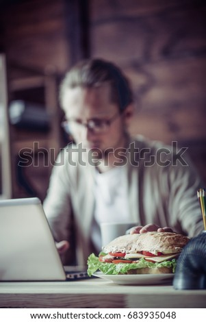 Freelancer typing with one hand, holding another hand for sandwich Young man working on project, keyboarding and drawing for sandwich.