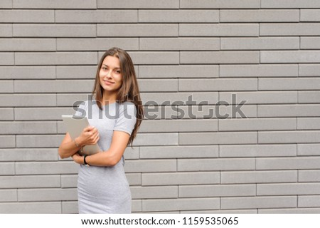 Freelancer, who studies the person who develops humanity, the concept of leisure for leisure. Portrait of a confident gifted excited, purposeful, intelligent,  teenage girl holding a digital tablet