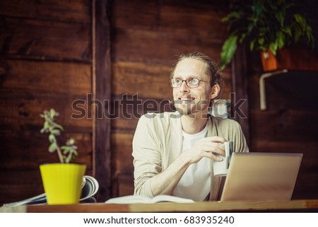 Freelancer working, drinking tea, looking aside. Man at home working looking in window, holding cup. #683935240