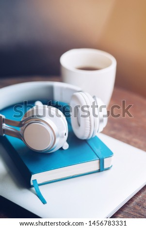 Freelancer workplace. Modern workplace with a laptop, cup of coffee, notebook and headphones on a wooden office desk background. Business and Freelance concept. Vertical shot #1456783331