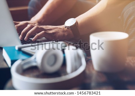 Freelancer workplace. Modern workplace with a laptop, cup of coffee, notebook and headphones on a wooden office desk. Business and Freelance concept. Horizontal shot #1456783421