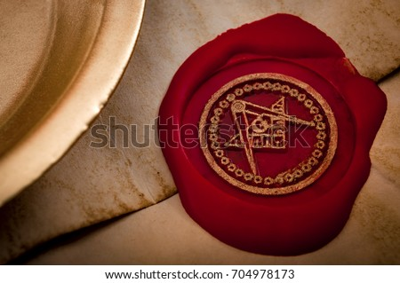 Freemason secret symbol concept with vintage letter under a candle, sealed with red wax seal with the square, the compass and the G letter in the middle, one of the most identifiable masonic symbols #704978173
