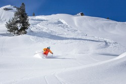 freeride skier skiing downhill through fresh powder snow