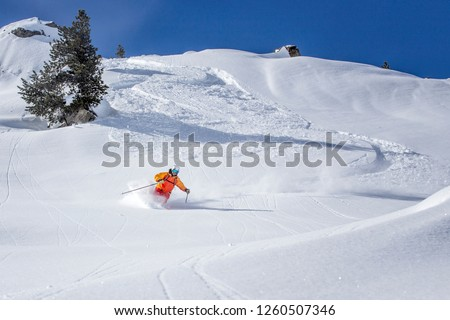 freeride skier skiing downhill through fresh powder snow #1260507346