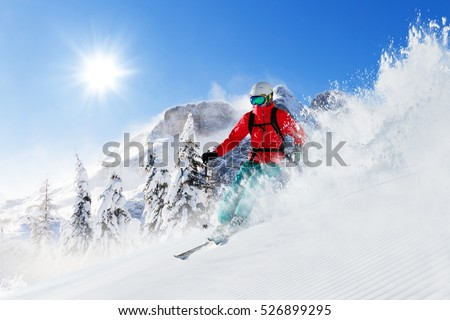Freeride skier with rucksack running downhill in freeze motion of snow powder. #526899295
