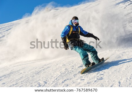 Freeride snowboarder rolls on a snow-covered slope leaving behind a snow powder against the blue sky #767589670