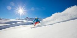 Freerider snowboarder running downhill in beautiful Alpine landscape. Fresh powder snow, blue sky on background.