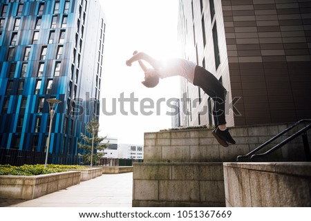 Freerunner is doing a backflip off a wall in the city.  #1051367669