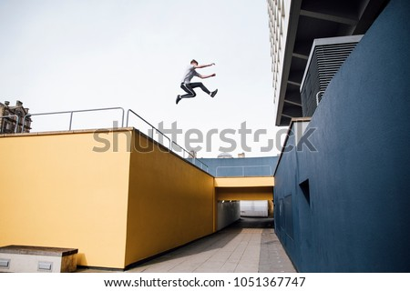Photo of Freerunner is jumping beween colourful buildings in the city.