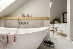 Freestanding bath with towels in grey modern bathroom