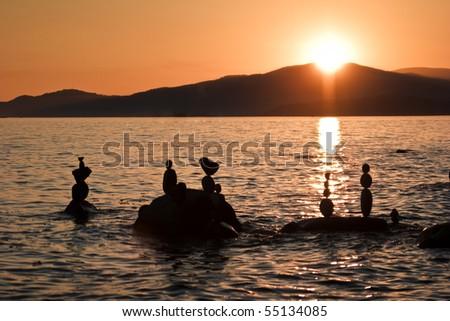 Freestanding rock sculptures in ocean at sunset - stock photo