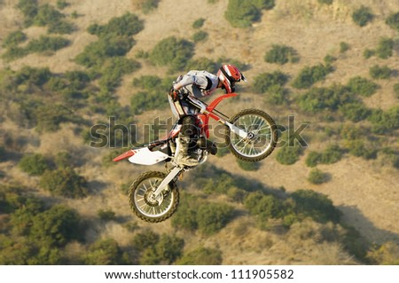 Freestyle Motocross Racer Performing Stunt - stock photo