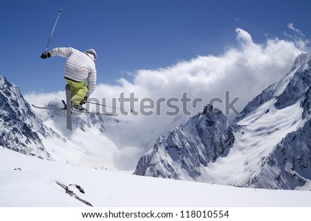 Freestyle ski jumper with crossed skis in high mountains