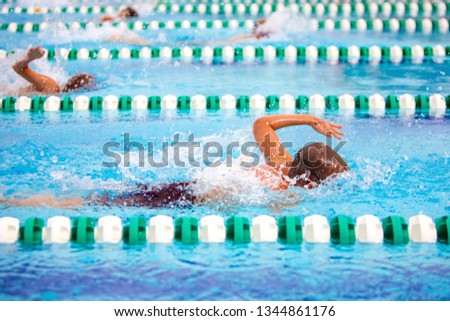Freestyle swimmers in a race, motion blur on swimmer #1344861176