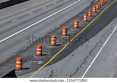 Freeway construction zone with a concrete roadway repaved with black asphalt, and line of orange barrel cones, in a transportation background