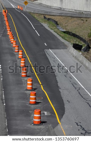 Freeway construction zone with line of orange barrel cones, on a concrete roadway repaved with black asphalt, in a transportation background