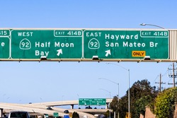 Freeway interchange in San Francisco Bay Area; Freeway signage providing information about the lanes going to 92 West towards Half Moon Bay and 92 East towards Hayward and San Mateo Bridge