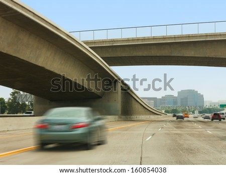 Freeway interchange, overpass, and fast cars.Concrete elevated roadway merging with multiple lane freeway.Fast cars, blurred motion.Fenced overpass. Blue sky, tall buildings in background.