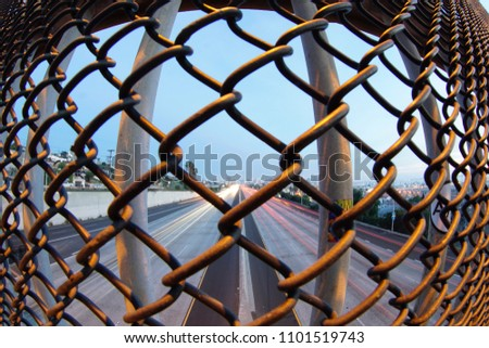 Freeway shot through a chainlink fence with slow shutter.