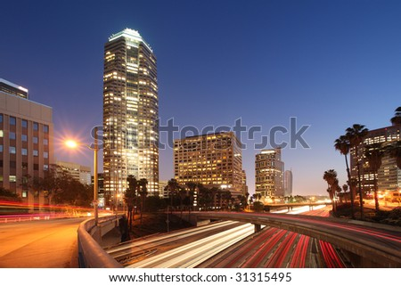 Freeway traffic in downtown Los Angeles at twilight.