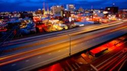Freeway traffic moves through Spokane, Washington as night falls