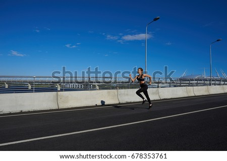 Freeze action shot of attractive determined young female athlete wearing black sportsbra and leggings running in the stadium, preparing for marathon or contest. Endurance and determination concept #678353761