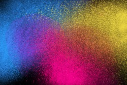 Freeze motion of colorful powder exploding isolated on dark black background. Abstract explosion design of yellow blue magenta, purple, violet dust. Particles cloud wallpaper.