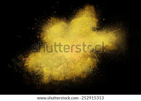 Freeze motion of colorful yellow powder exploding isolated on black dark background. Abstract design of color dust cloud. Particles explosion screen saver, wallpaper, brush