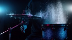 Freeze motion of drummer hitting drums with water splashes, isolated on black background