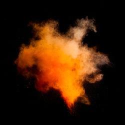 Freeze motion of orange dust explosion isolated on black background