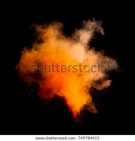Freeze motion of orange dust explosion isolated on black background #749784415