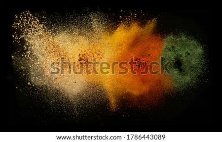 Freeze motion of various spice explosion, abstract culinary background. Isolated on black background