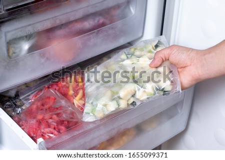 Freezer and frozen vegetables, a person taking food from the freezer, closeup