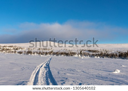 Freezing landscape from the Swedish mountains or fjeld, in bright sunlight and a snow mobile track leading up to the top
