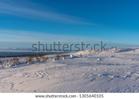 Freezing landscape from the top of the Swedish mountains or fjeld, in bright sunlight with signs for a snow mobile route