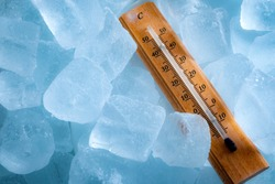 Freezing temperatures and cold weather concept with a vintage thermometer surrounded by blue ice showing sub zero temperature with copy space