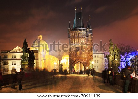 Freezy foggy night snowy Prague with Charles Bridge Tower - stock photo