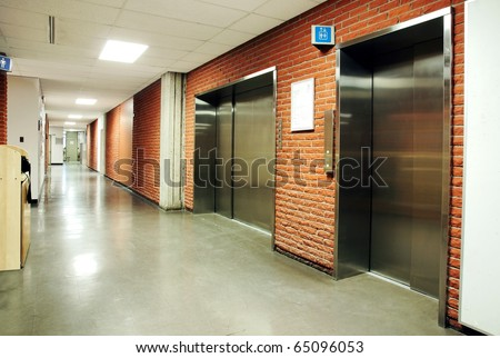 Freight and regular steel door elevators with signs in an empty hallway of modern building. Can be office, school, hospital.